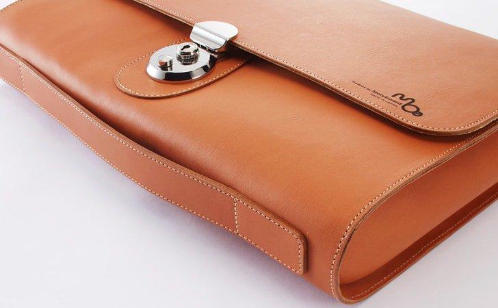 バッグの底に丸みと手首を挟むガイドが特徴の革のクラッチバッグ